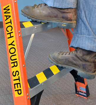 Ladder label reminds workers to watch step.