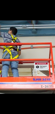 Sign on platform reminds worker to use PPE
